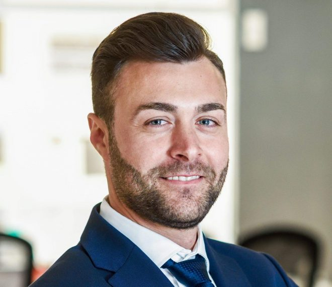 Caucasian businessman leader looking at camera in modern office with multi-ethnic businesspeople working at the background. Teamwork concept. Young man with beard wearing blue suit.